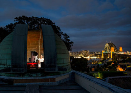 On the left, Observatory dome is open to show telescope, on the right in the distance we see Sydney Harbour Bridge lit up in the night