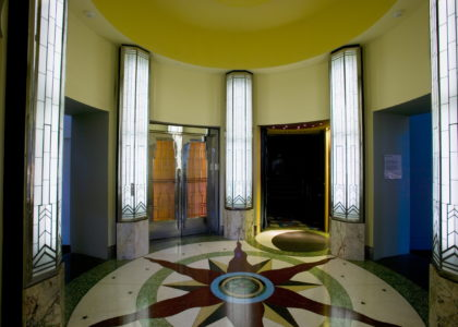 Circular foyer of Kings Cinema with a red sun pattern in the floor tiles and tall, bright lights around the room