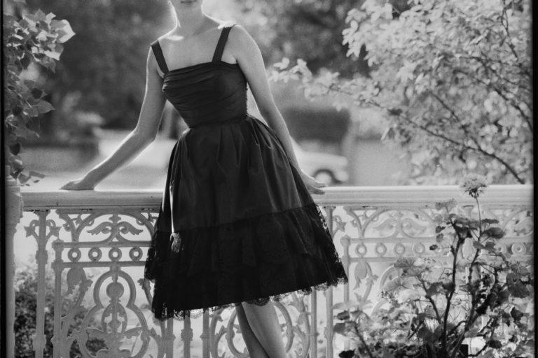 Model in knee length black cocktail dress on the verandah of a Victorian house