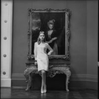 Model wearing a knee length white dress standing in front of painted portrait