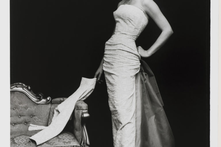 Model stands alongside an antique couch wearing a strapless full length evening gown