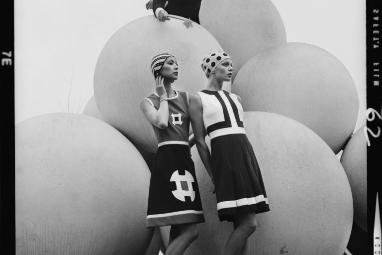 Models wearing sleeveless knee length dresses and tight fitting caps standing in front of a large sculpture