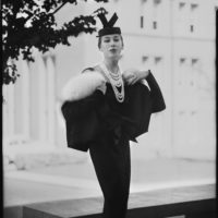 Model in black suit with pill box hat and multiple white beaded necklaces