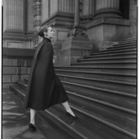 Model wearing a black woollen coat, walking up the stairs of an old building