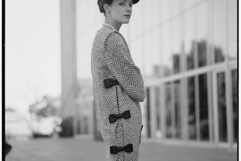 Model wearing tunic over skirt and beret. The tunic has black bows down the side.