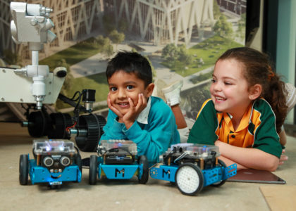 Two small primary school aged children playing with robots