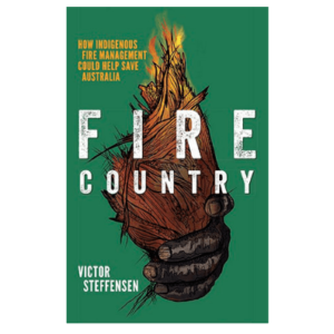 Book cover Fire Country by Victor Steffensen showing a First Nations hand holding a burning firestick